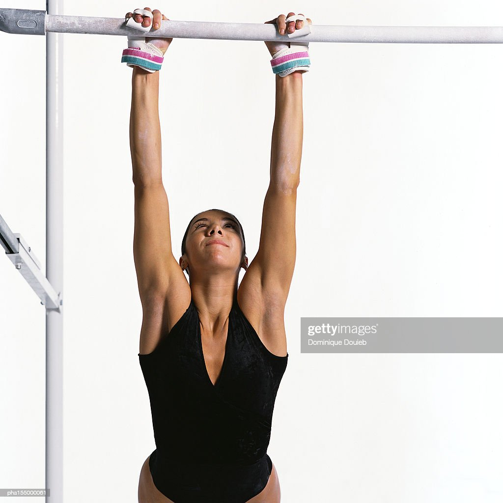 Young female gymnast holding onto parallel bar. : Stockfoto