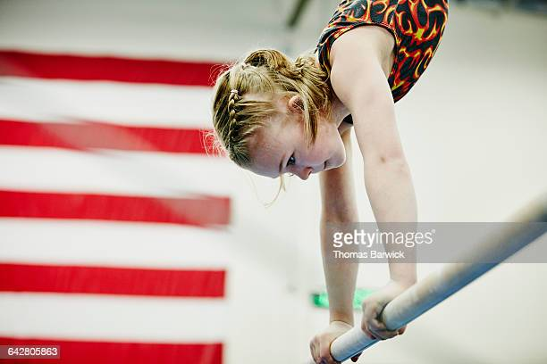 young female gymnast in handstand on bar - gymnastiek stockfoto's en -beelden