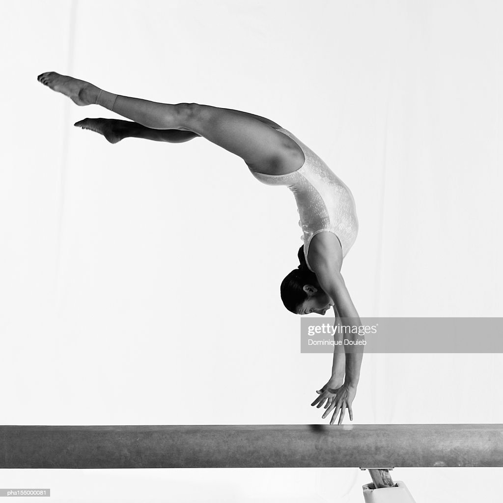 Young female gymnast on balance beam performing exercise, mid-flight, side view. B&w. : Stockfoto