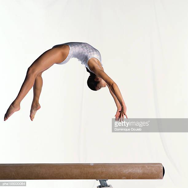 Young female gymnast on balance beam performing exercise, mid-flight, side view.