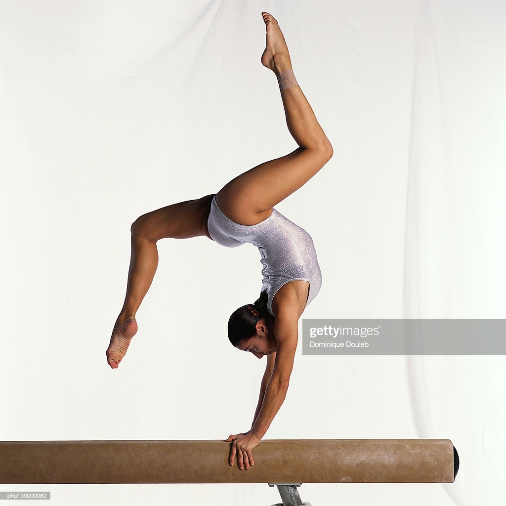 Young female gymnast on balance beam performing exercise, side view. : Stockfoto