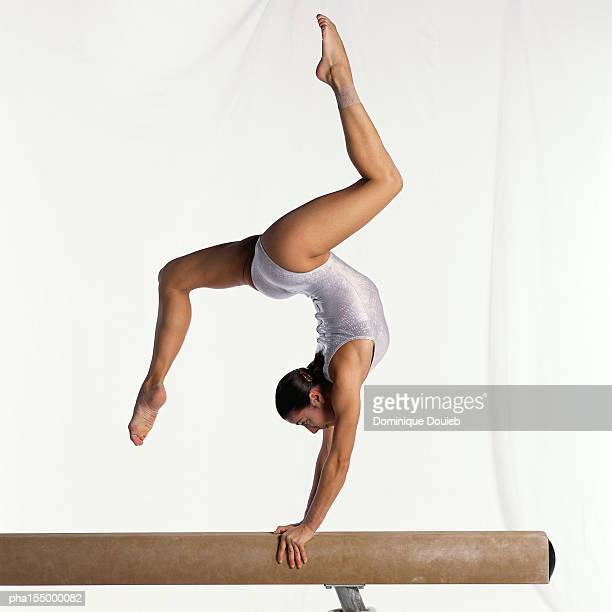 Young female gymnast on balance beam performing exercise, side view.
