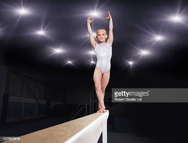 young female gymnast performing on balance beam - little girls leotards stock photos and pictures