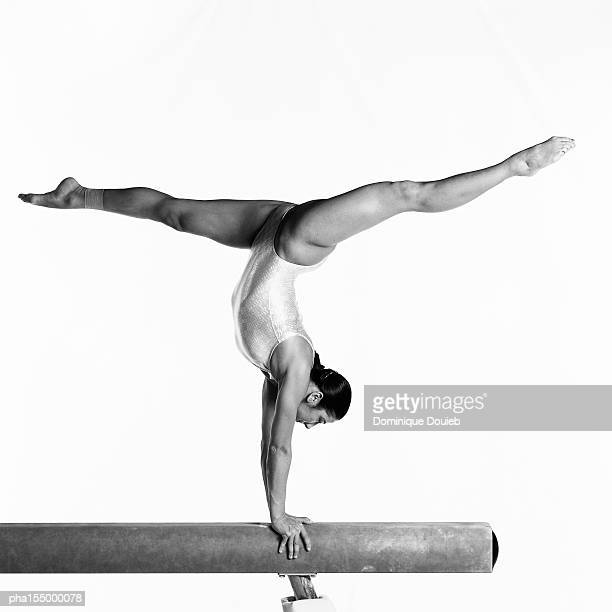 Young female gymnast performing on balance beam, side view, b&w.