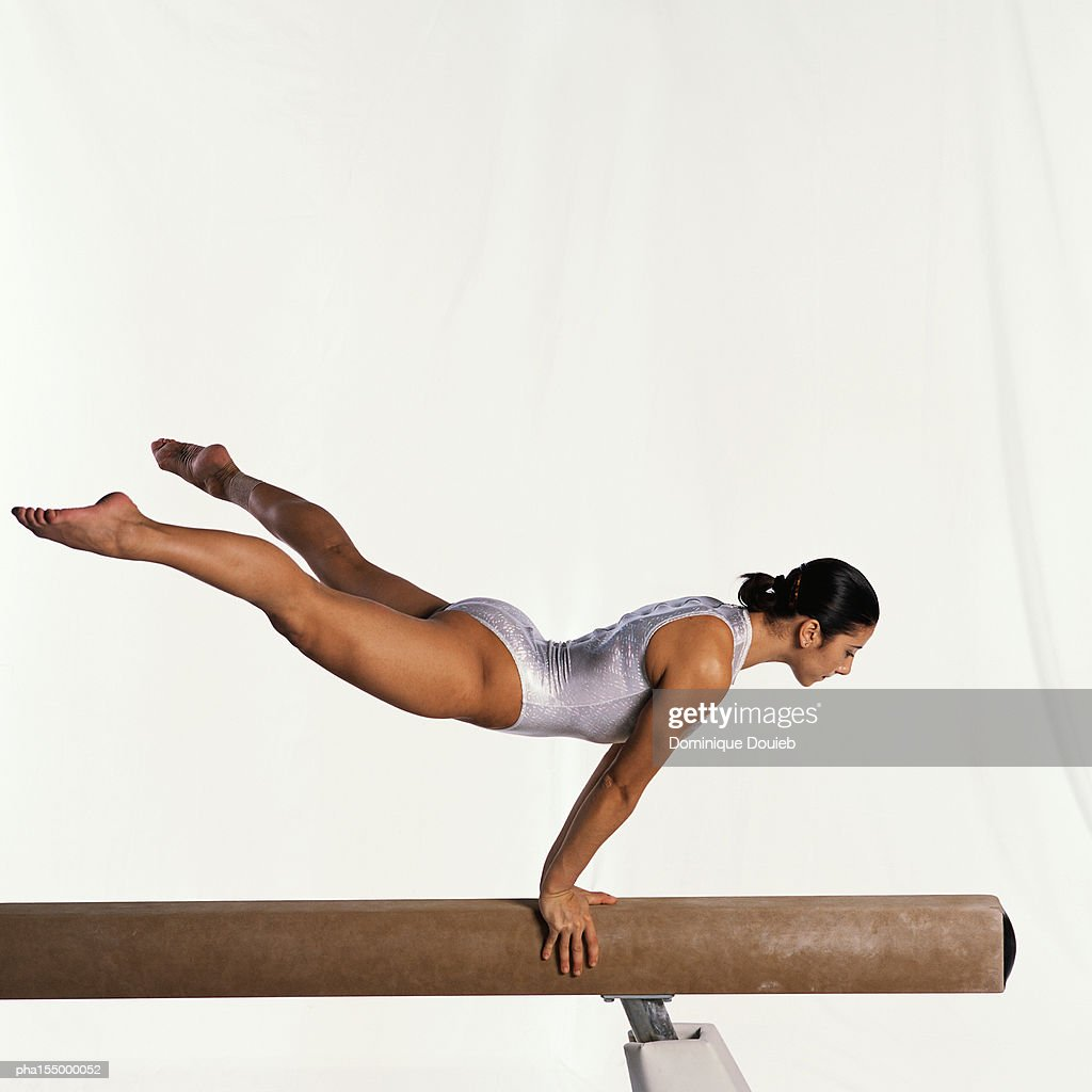 Young female gymnast performing routine on balance beam, side view. : Stockfoto