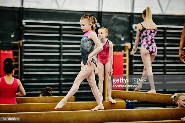 Young female gymnast practicing on balance beam