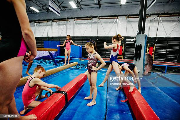 Young female gymnast taping pad to balance beam