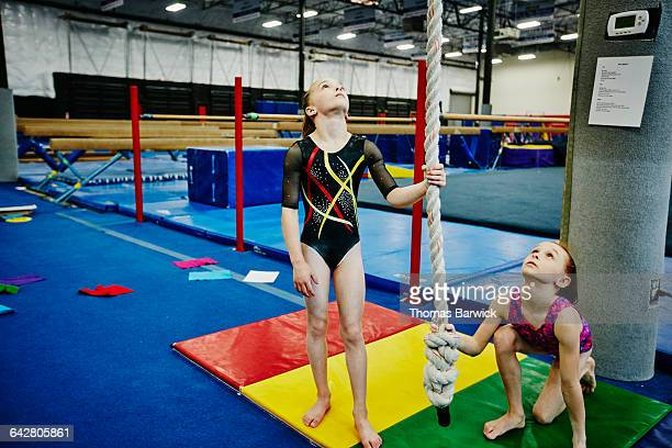 young female gymnasts holding rope for teammate - leanincollection stock pictures, royalty-free photos & images