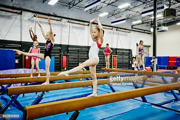young female gymnasts practicing on balance beams - gymnastiek stockfoto's en -beelden
