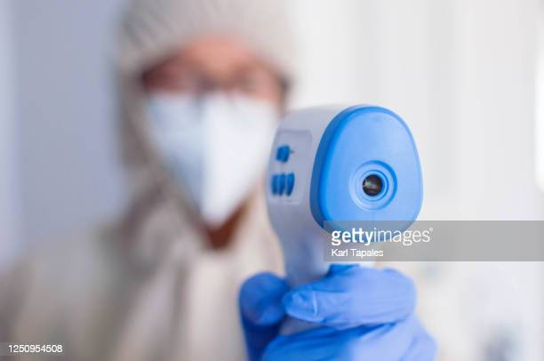 a young female health worker is using an infrared thermometer to check body temperature - filipino ethnicity and female not male fotografías e imágenes de stock