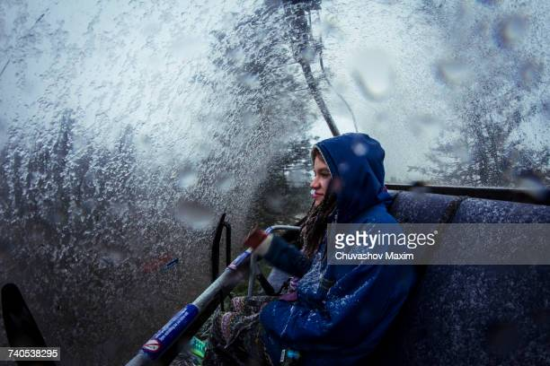 Young female hiker in chairlift during mountain snowstorm