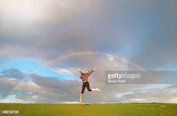 young female hiker jumping mid air below rainbow - luck stock pictures, royalty-free photos & images