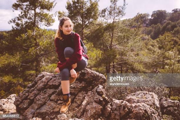 Jeune randonneuse assis sur un rocher dans les bois