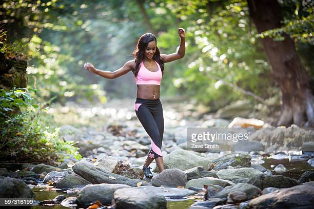 Young female hiker stepping over forest river rocks