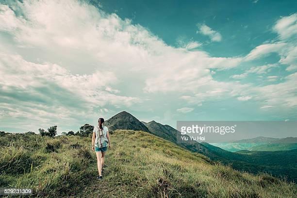 Young female hiker walking along mountain trail