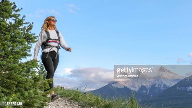 young female hiker walks along footpath - ascent xmedia stock pictures, royalty-free photos & images