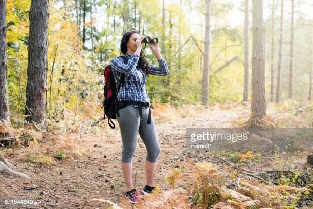 Young female hiker watching through binoculars wild birds