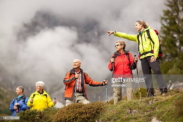 young female hiking guide showing senior group surrounding mount - guidance stock pictures, royalty-free photos & images