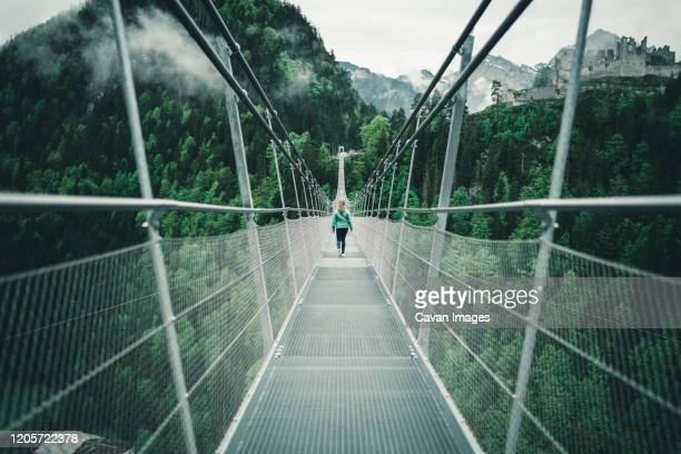 young female hiking over suspension rope bridge in alpine environment - suspension bridge stock pictures, royalty-free photos & images