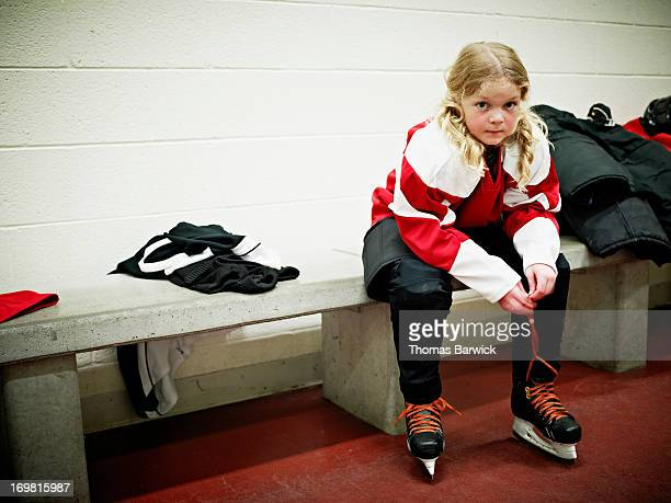 Young female hockey player in locker room