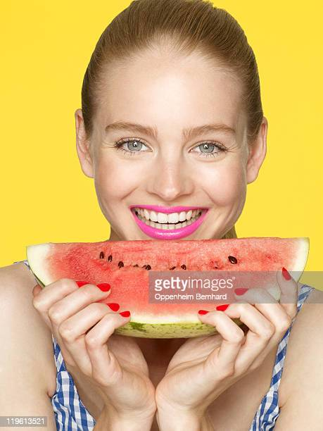 young female holding a slice of watermelon