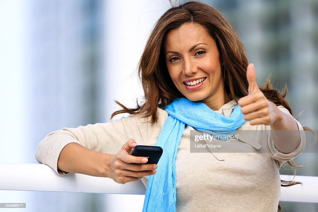 Young female holding cell phone and gesturing thumbs up : Stock Photo
