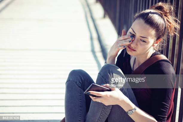 Young female holding her telephone and crying alone