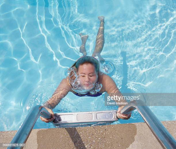 Young female holding ladder underwater, overhead view
