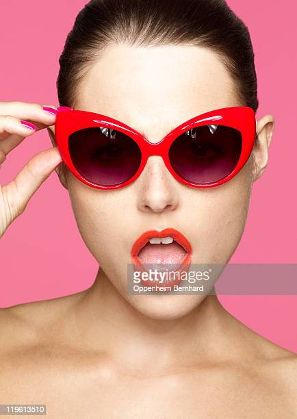 young female holding onto sunglasses