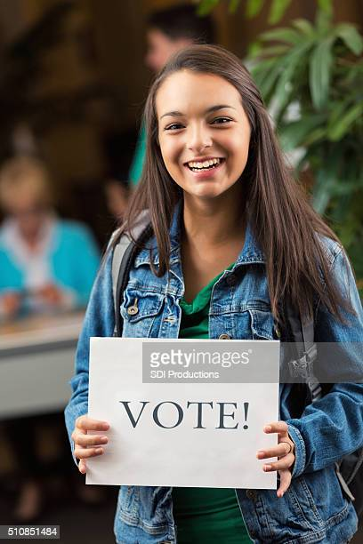 Young female holds 'Vote!' sign at polling place
