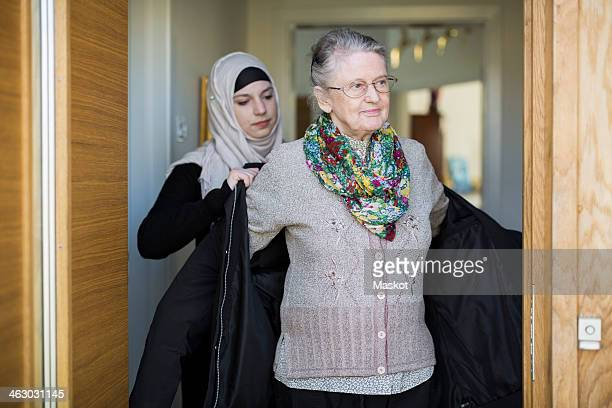 Young female home caregiver assisting senior woman in wearing jacket at home