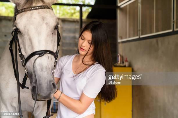 jonge vrouwelijke ruiter een hoofdstel zetten haar paard - paard paardachtigen stockfoto's en -beelden