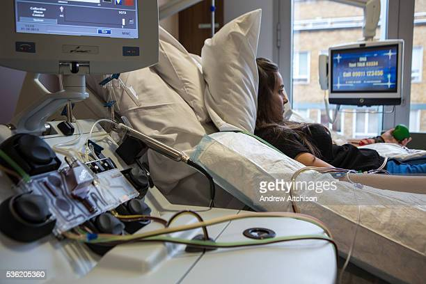 Young female hospital patient lies bed while attached to a medical transfusion device in the London clinic, London, United Kingdom. Her stem cells...