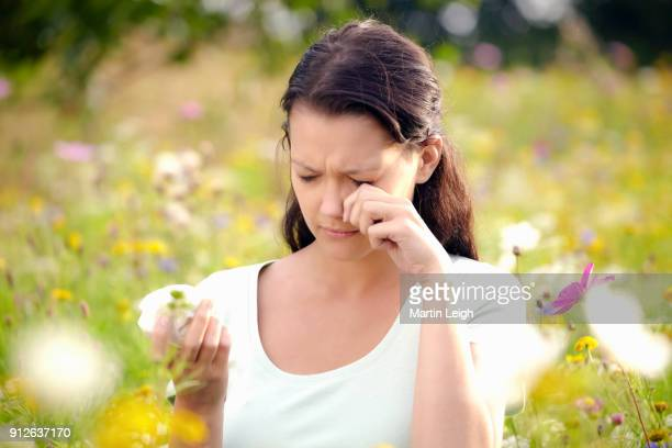Young female in a wild flower meadow suffering from hay fever.