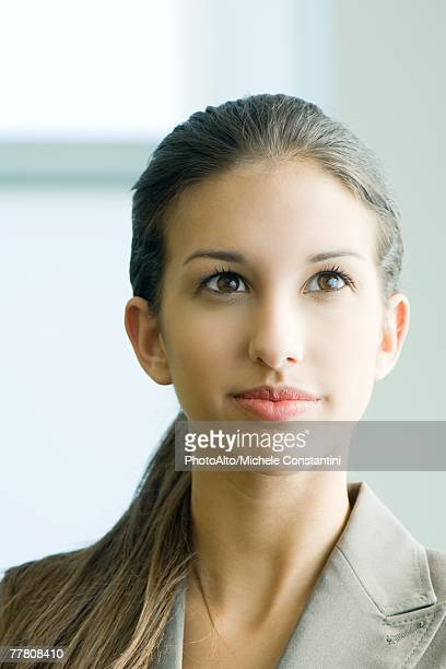 Young female in business attire smiling, looking up, portrait