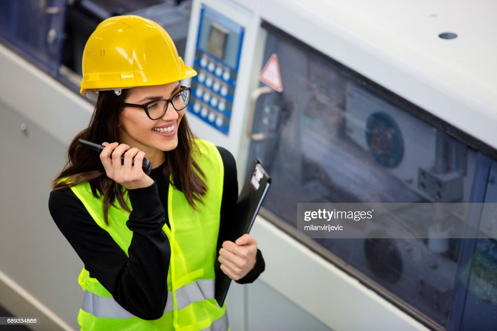 Young female in factory with yellow helmet and wifi phone : Stock Photo