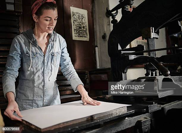 Young female in letterpress studio placing paper,