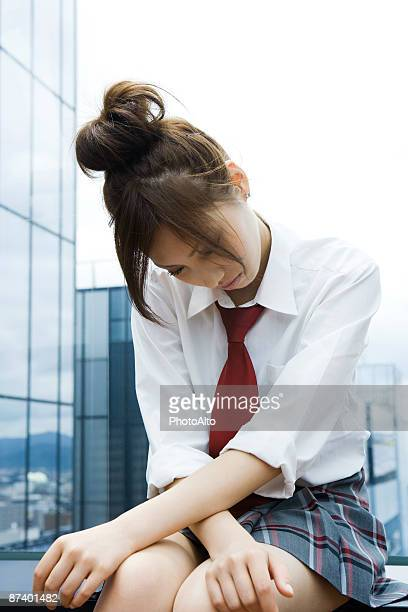 young female in school uniform sitting with head down - japanese short skirts stock pictures, royalty-free photos & images
