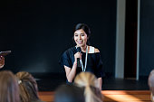Young female influencer speaks with crowd during seminar