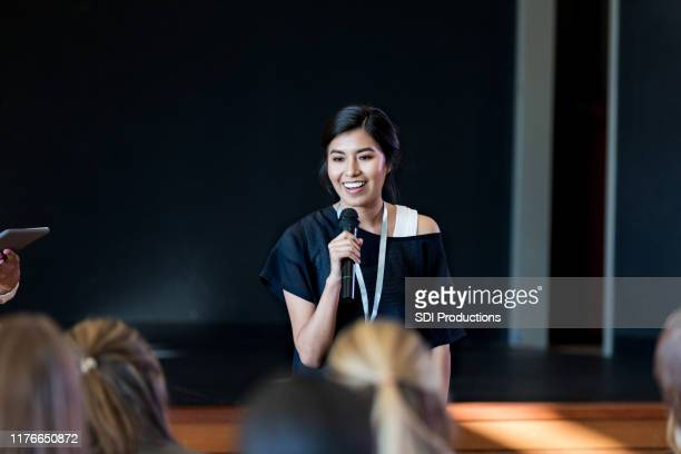 young female influencer speaks with crowd during seminar - presentazione discorso foto e immagini stock