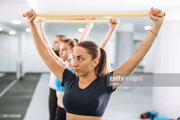 Young female instructor on fitness class with kettlebells