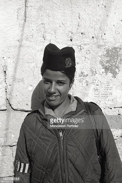 A young female Israeli soldier photographed smiling against a stone wall in the Old City in Jerusalem Jerusalem December 1969