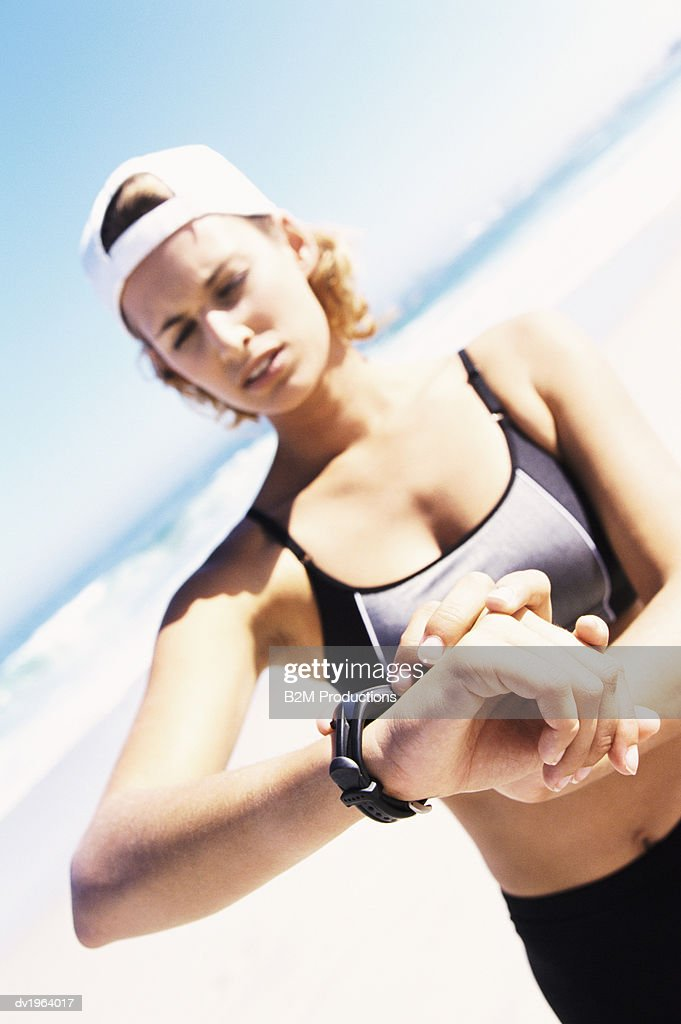 Young Female Jogger Checking the Time on Her Wristwatch Standing on a Beach : Stock Photo