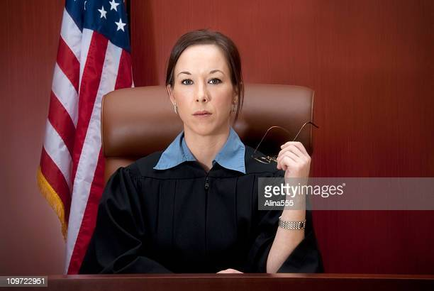young female judge at the bench with serious look - judge stock pictures, royalty-free photos & images