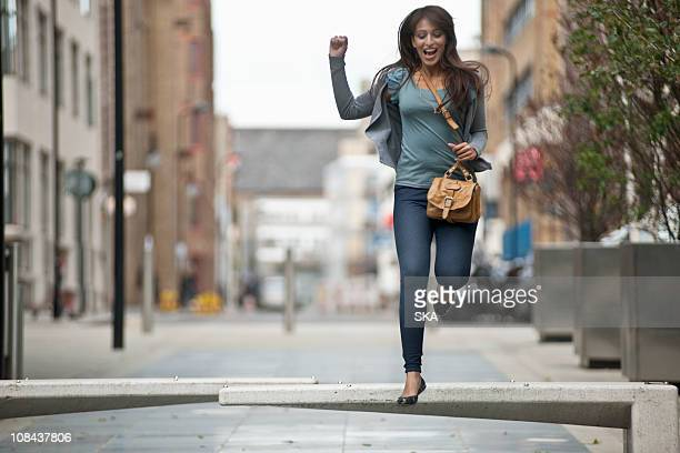 Young female jumping in street