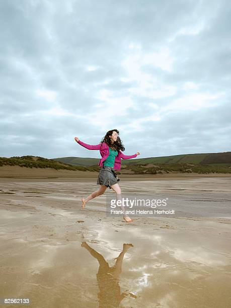 Young female jumping on beach