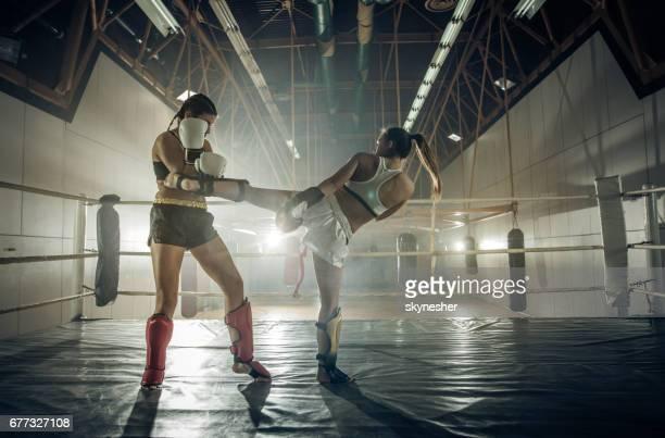 Unga kvinnliga kick boxare striderna i boxningsringen.