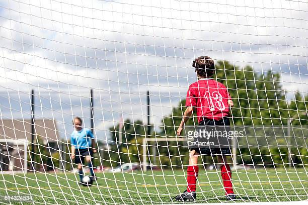 young female kicking a soccer ball towards a male goalie - fat goalkeeper stock pictures, royalty-free photos & images