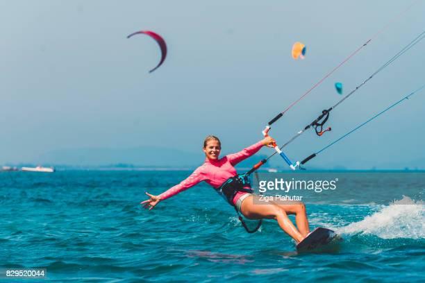 young female kiteboarder enjoying kiteboarding - kiteboarding stock photos and pictures