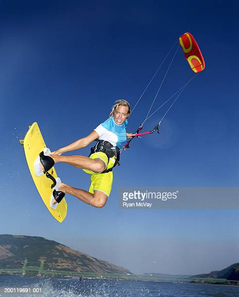 Young female kiteboarder grabbing board in mid-air, low angle view
